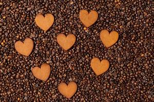 biscoitos de gengibre em forma de coração no fundo de grãos de café foto