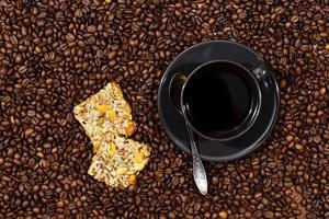 vista superior da caneca de café preta e biscoitos no fundo dos grãos de café foto