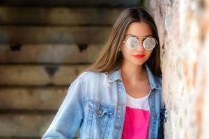 retrato ao ar livre de mulher jovem e bonita em óculos de sol foto