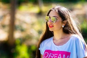 retrato ao ar livre de uma jovem bonita e emocional com óculos de sol foto