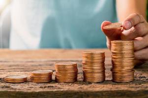 uma pessoa segurando uma moeda com uma pilha de moedas em uma mesa de madeira, conceito de investimento