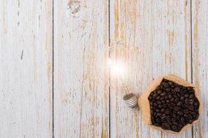 grãos de café e uma lâmpada emitindo energia em um fundo de madeira