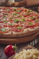 pizza brasileira com molho de tomate, mussarela, tomate, parmesão e manjericão foto