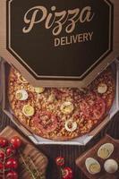 pizza brasileira com mussarela, milho, bacon, ovos, tomate e orégano em uma caixa de entrega foto