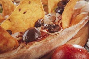 pizza com mussarela, cebola, calabresa, azeitona preta, pimentão verde, nachos e orégano