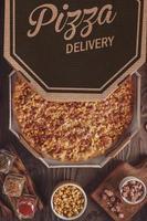 pizza com mussarela, milho, bacon e orégano em caixa de entrega