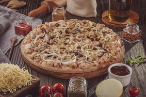 pizza com molho barbecue, grelhada, frango, cebola e orégano foto