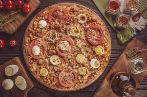 pizza brasileira com mussarela, milho, bacon, ovos, tomate e orégano foto