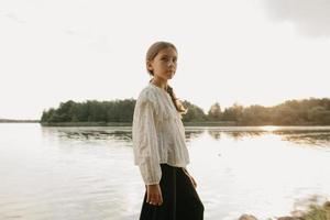 um retrato desfocado de uma jovem que está caminhando na costa do lago ao pôr do sol
