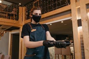uma garçonete que usa avental, máscara médica e luvas médicas descartáveis está entregando um terminal de pagamento sem fio a um cliente em um restaurante
