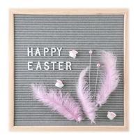 cartão postal com texto feliz Páscoa com penas cor de rosa e coelhos de brinquedo