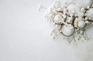 ovos pintados de páscoa, flores e penas em um fundo branco texturizado