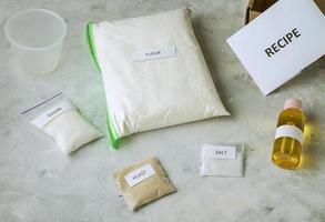 um conjunto de ingredientes para assar pão caseiro, incluindo farinha de trigo integral, sal, açúcar, óleo de girassol ou azeite e fermento