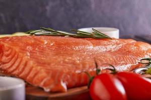 Filé de salmão cru com pimenta, sal, endro, limão, alecrim e tomate cereja foto