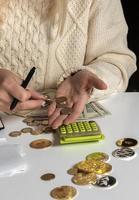 close-up de uma mulher calculando dinheiro e escrevendo em um caderno foto