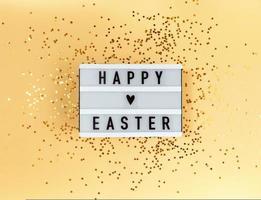 Feliz Páscoa em uma mesa de luz e confetes em um fundo amarelo