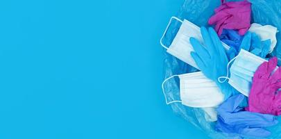 Resíduos de coronavírus pandêmicos médicos, máscaras faciais e luvas de látex em um saco de lixo sobre um fundo azul