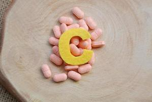 pílulas overtop de vitamina c em fundo de madeira, conceito de imunidade e nutrição foto