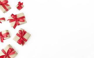 caixas de presente embrulhadas em papel artesanal com fitas vermelhas e laços em um fundo branco, planície festiva com espaço de cópia foto