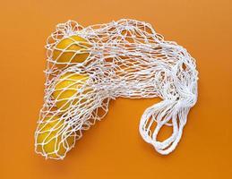saco ecológico de algodão de cordão branco com laranjas dentro em um fundo laranja, monocromático simples plano leigo ecologia zero desperdício foto