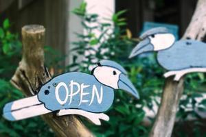 uma placa de negócios que diz aberta na entrada de uma porta suspensa de um café ou restaurante