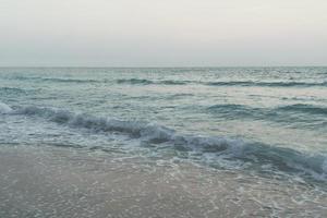 tom vintage desbotado das ondas do mar na praia durante o verão foto