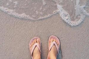 vista superior dos pés de uma mulher de chinelos em uma praia arenosa com as ondas do mar