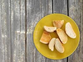 Pão fatiado em um prato amarelo no fundo da mesa de madeira foto