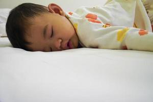 bebê asiático dormindo de bruços foto