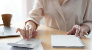 mulher usando calculadora e laptop