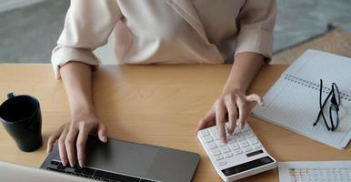 vista superior de uma mulher trabalhando em um laptop e uma calculadora