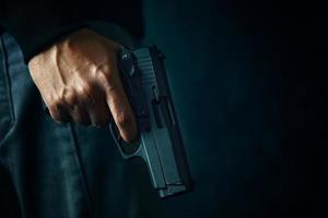 criminoso com revólver em fundo escuro foto