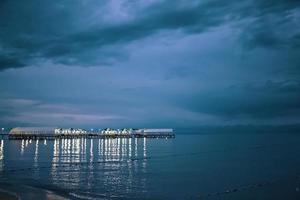 paisagem crepuscular do cais estendendo-se para o mar foto