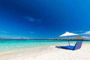 espreguiçadeiras com guarda-sol na praia de areia perto do mar foto