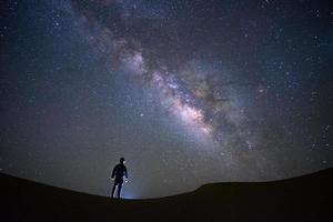Via Láctea com um homem parado olhando no deserto de alcatrão, Jaisalmer, Índia foto