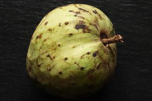fruta de cherimóia inteira em fundo de ardósia foto