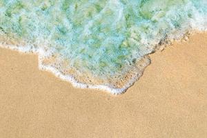 ondas suaves com espuma de oceano azul na praia de areia