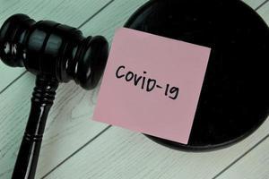 covid-19 escrito em um bloco de notas com o martelo isolado na mesa de madeira