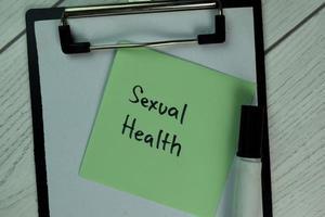 saúde sexual escrita no bloco de notas isolado na mesa de madeira