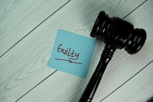 culpado escrito no bloco de notas com o martelo isolado na mesa de madeira