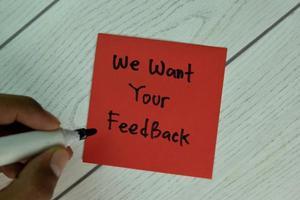 queremos seu feedback escrito em bloco de notas isolado em mesa de madeira