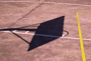 silhueta da sombra da cesta de basquete de rua na quadra foto