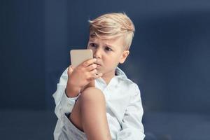 garotinho usando telefone celular sem acreditar