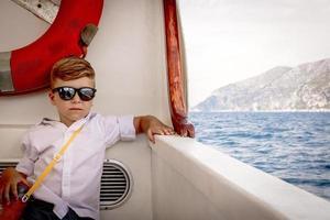 garotinho viajando no convés do navio de passageiros foto