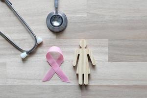 fita rosa e estetoscópio com mulheres em fundo de madeira foto