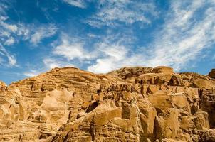 montanhas rochosas marrons e céu azul com nuvens foto