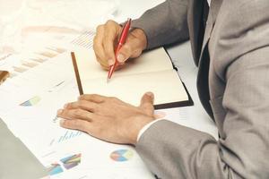 homem de negócios escrevendo em um caderno foto