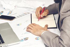 empresário escrevendo em um caderno foto