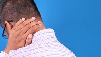 homem segurando o pescoço com dor por trás foto