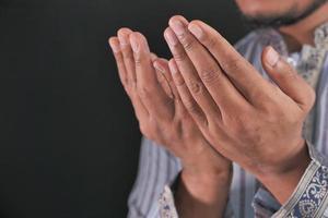 mãos de homem orando em fundo preto foto